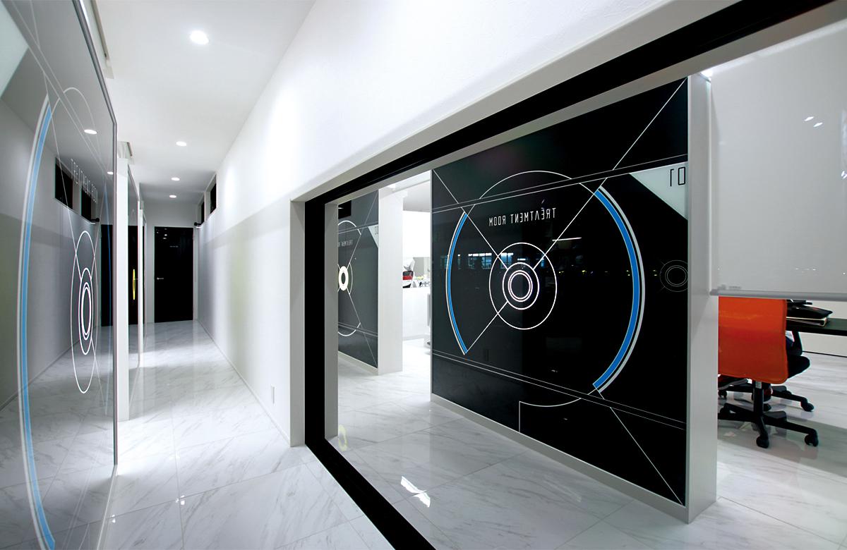 近未来イメージでデザインされた光壁の隙間から各治療ブースへ