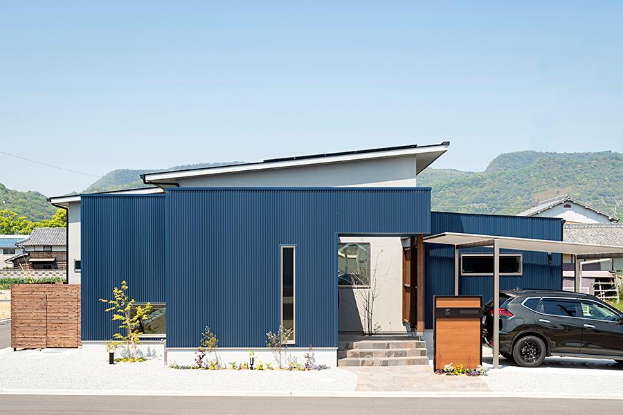青空に映えるダークブルーの外壁