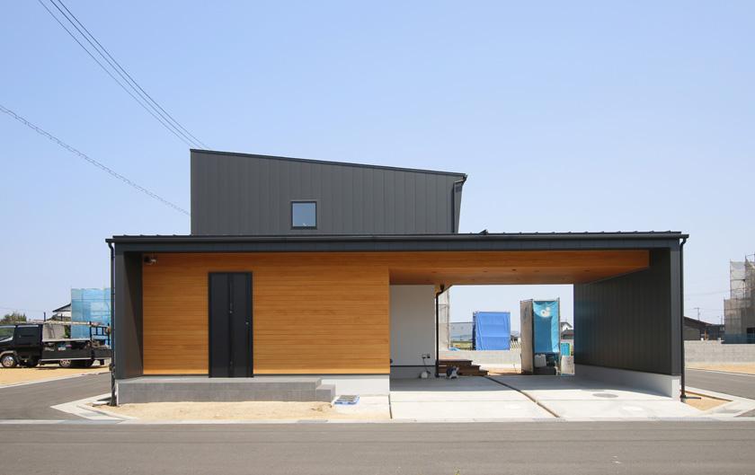 大きなガレージと黒と木の組み合わせが目を惹く外観