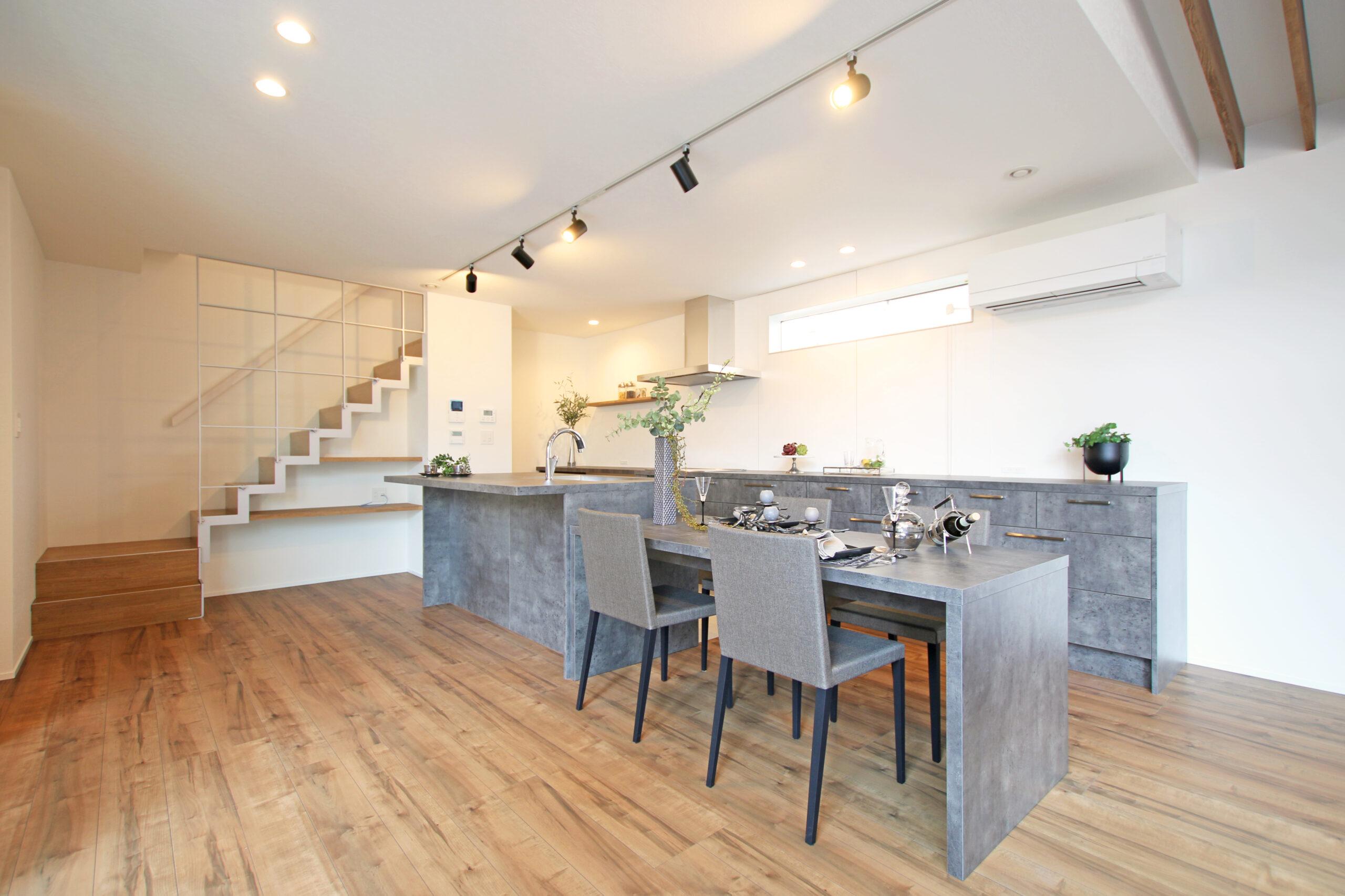モルタル風のイメージで統一したキッチンとダイニング、カップボード。LDKの雰囲気が引き締まります。