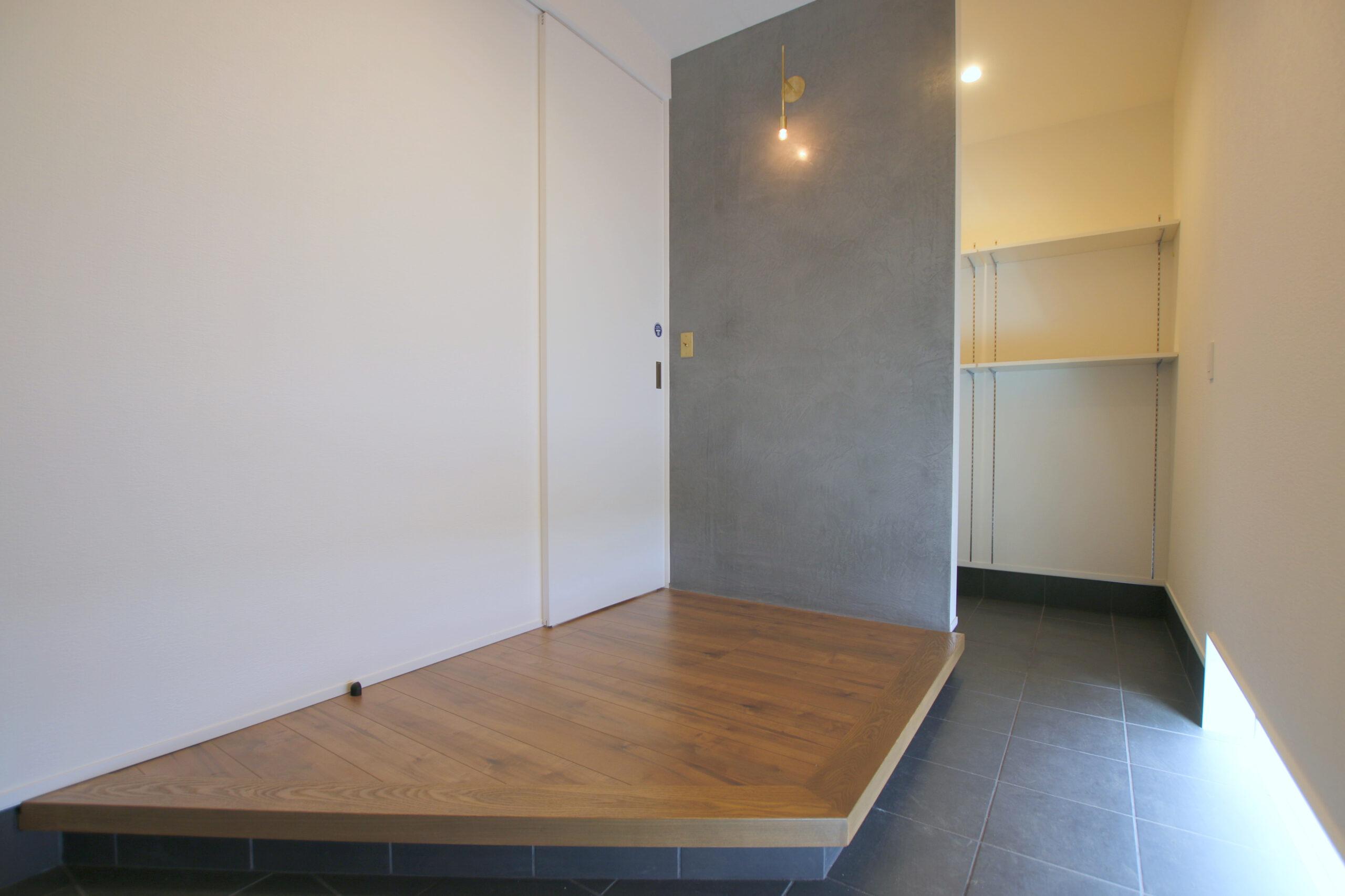 モルタル風の塗り壁とお気に入りの照明が出迎えます。
